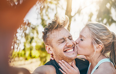 Buy stock photo Shot of a young woman kissing her boyfriend on the cheek outside