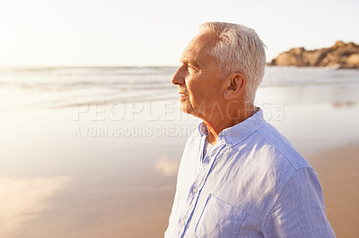 Buy stock photo Shot of a senior man standing on the beach and looking out towards the sea