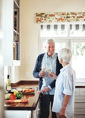 Buy stock photo Cropped shot of a senior couple toasting with wine while preparing a meal at home