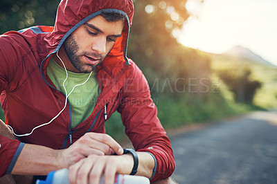 Buy stock photo Shot of a young man drinking water and checking his watch while out for a run