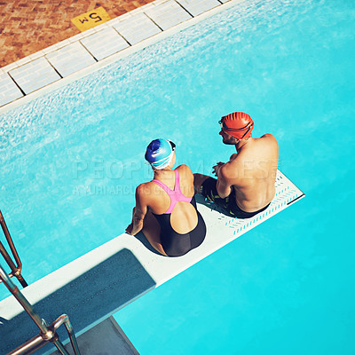 Buy stock photo High angle shot of two swimmers sitting on a diving board above a swimming pool