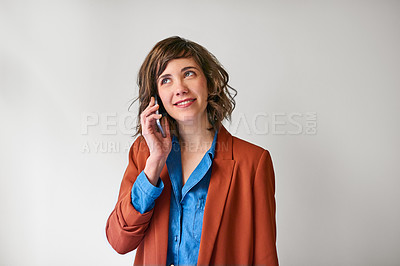 Buy stock photo Shot of an attractive young woman using her cellphone against a grey background