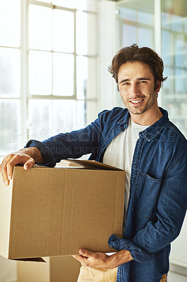 Buy stock photo Shot of a handsome young man carrying a box while moving house