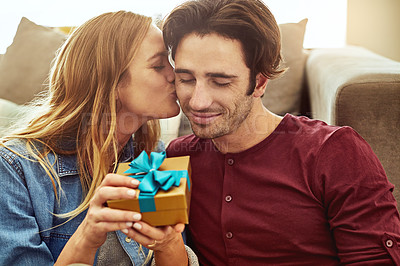 Buy stock photo Cropped shot of a young woman kissing her boyfriend in gratitude while holding a gift