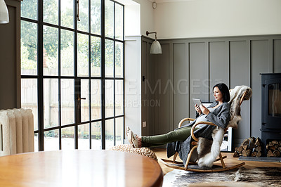Buy stock photo Shot of an attractive and pregnant young woman relaxing on a rocking chair