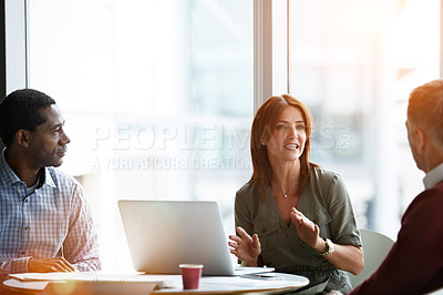 Buy stock photo Shot of three professional businesspeople meeting in their office