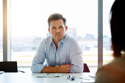 Buy stock photo Shot of a mature businessman sitting in the boardroom during a meeting