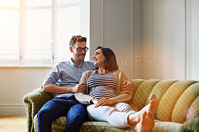 Buy stock photo Shot of an affectionate young couple relaxing on the sofa at home