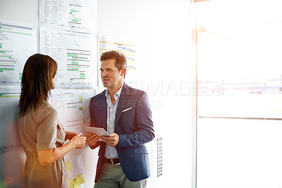Buy stock photo Shot of a mature businessman talking to a female colleague in the office