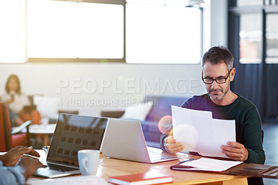 Buy stock photo Shot of a mature businessman looking over some paperwork in the office