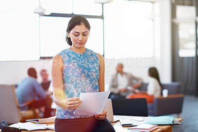 Buy stock photo Shot of a young businesswoman reading through some paperwork in her office