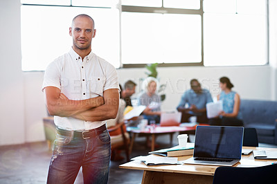 Buy stock photo Shot of a handsome young businessman standing with his arms folded in the office