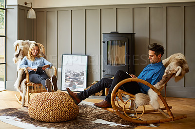 Buy stock photo Shot of a couple using digital tablets while relaxing on rocking chairs at home