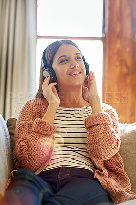 Buy stock photo Shot of a smiling young woman sitting on her sofa listening to music on headphones
