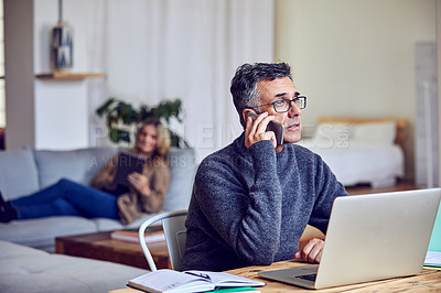Buy stock photo Shot of a handsome and mature man working from home with his wife in the background