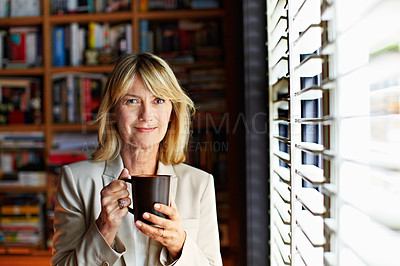 Buy stock photo Portrait of a mature businesswoman drinking coffee while standing at a window in her home