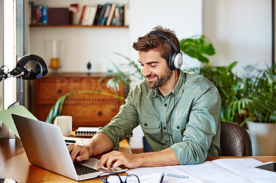 Buy stock photo Shot of a young man sitting at home wearing headphones and working on a laptop