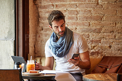Buy stock photo Shot of a handsome young man using his cellphone while sitting in a cafe