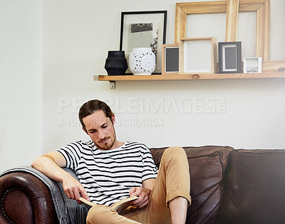 Buy stock photo Shot of a handsome young man reading a book while sitting on a sofa at home