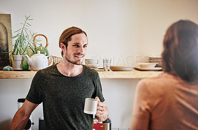 Buy stock photo Shot of an affectionate young couple having a conversation in the kitchen