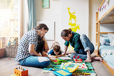 Buy stock photo Shot of a young family of three drawing while sitting on the floor of a child's bedroom