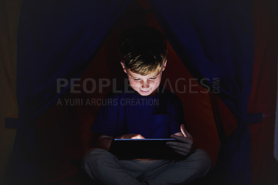 Buy stock photo Shot of a little boy using a tablet while sitting down on his bed