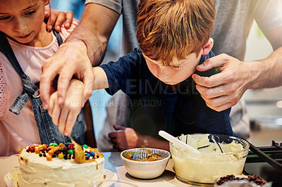 Buy stock photo Shot of a young father baking a cake with his son and daughter