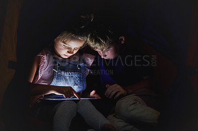Buy stock photo Shot of a little girl and her brother using a tablet while sitting down on a bed