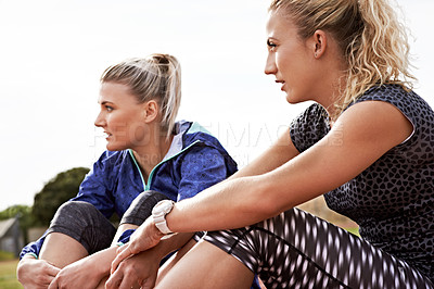 Buy stock photo Shot of two young athletic women sitting out on the track