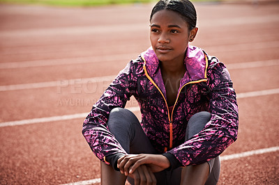 Buy stock photo Shot of an athletic young woman sitting out on the track