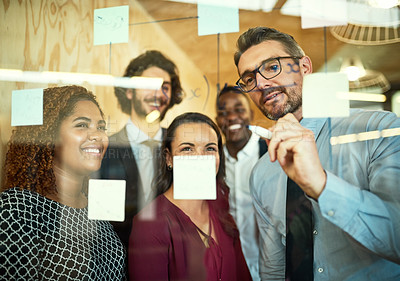 Buy stock photo Cropped shot of coworkers using sticky notes on a glass wall during a meeting in the office