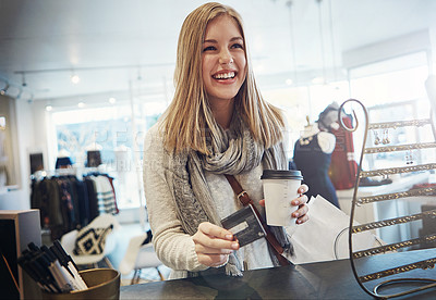 Buy stock photo Shot of a young woman ready to pay for her goods in a clothing store