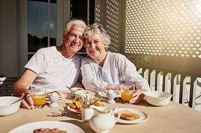 Buy stock photo Shot of a happy senior couple having a leisurely breakfast on the patio at home