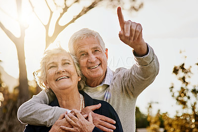 Buy stock photo Shot of a happy senior man pointing something out to his wife outdoors