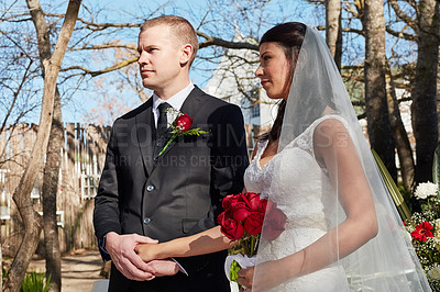 Buy stock photo Cropped shot of a bride and groom at their outdoor wedding ceremony