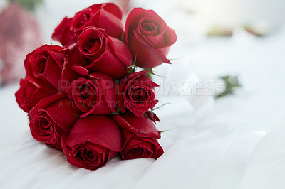 Buy stock photo Shot of a bunch of red roses lying on a bed