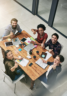 Buy stock photo High angle portrait of a group of colleagues giving a thumbs up during a meeting in a modern office