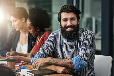 Buy stock photo Portrait of a designer sitting in an office with his colleagues in the background