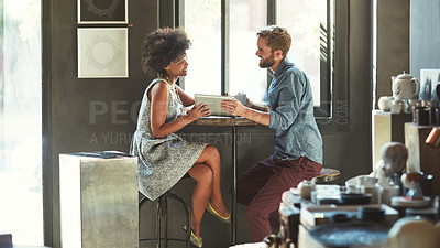 Buy stock photo Cropped shot of a young couple using a digital tablet in a cafe