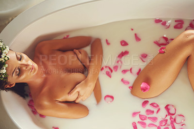 Buy stock photo Portrait of a beautiful nude woman relaxing in a bathtub filled with milk and flower petals at home