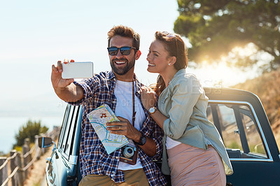 Buy stock photo Cropped shot of an affectionate couple taking a selfie while enjoying a road trip