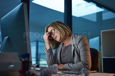 Buy stock photo Cropped shot of a businesswoman looking stressed while working late in the office