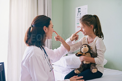 Buy stock photo Shot of a friendly doctor sitting in front of her young patient