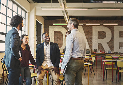 Buy stock photo Shot of a team of laid-back businesspeople chatting during their break in the office