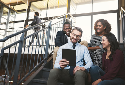 Buy stock photo Shot of a diverse group of colleagues having an impromptu meeting with a tablet on the stairs