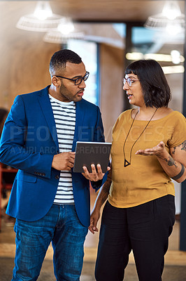 Buy stock photo Shot of two young designers working together on a digital tablet in an office