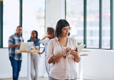Buy stock photo Shot of a young woman using a digital tablet in a modern office with her colleagues in the background