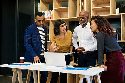 Buy stock photo Shot of a group of creative businesspeople discussing something on a laptop