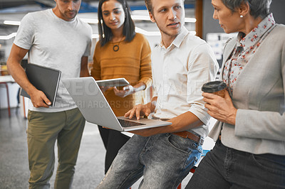 Buy stock photo Cropped shot of a handsome young businessman showing his colleagues something on a laptop