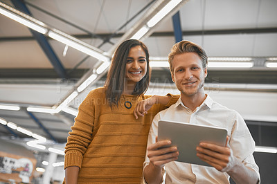 Buy stock photo Cropped portrait of two young businesspeople looking at a tablet in their office